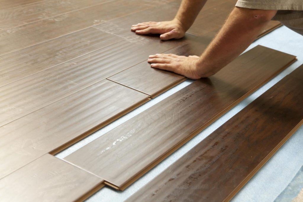 man installing wooden tiles